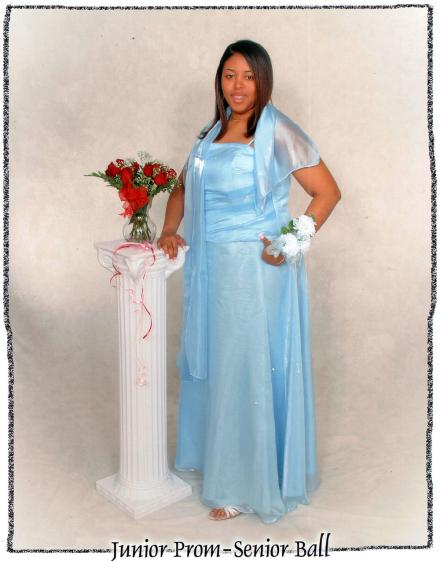 Sharee as a junior in high school wearing a prom dress and posing for a full length photo with a corsage on her wrist.