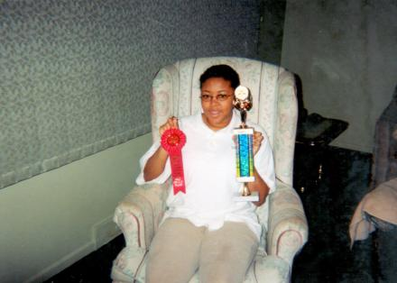 15-year-old Sharee sits in a recliner holding a ribbon in one hand and a trophy in the other.