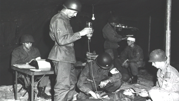 Soldiers tending a wounded solider with an IV morphine drip