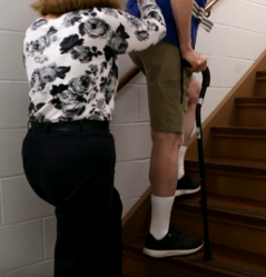 Donald navigating stairs with a cane and a nurse.