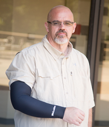 Mr. Lane, a middle aged man with his right arm in a compression sleeve